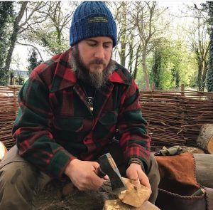 Bogman wearing bright blue bogman beanie while chopping wood